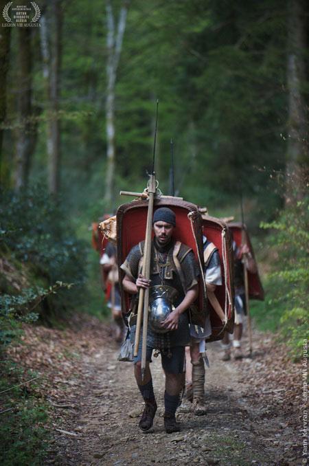 """Ce légionnaire de la Legio VIII Augusta, transformé en """"mule de Marius"""", porte ses sarcinae suspendues à une furca de bois. Il vient de parcourir quelques miles et va profiter d'un court moment de repos:""""Consistere! Laxate! Ostiose!"""" Ah!, les beautés de l'archéologie expérimentale....."""
