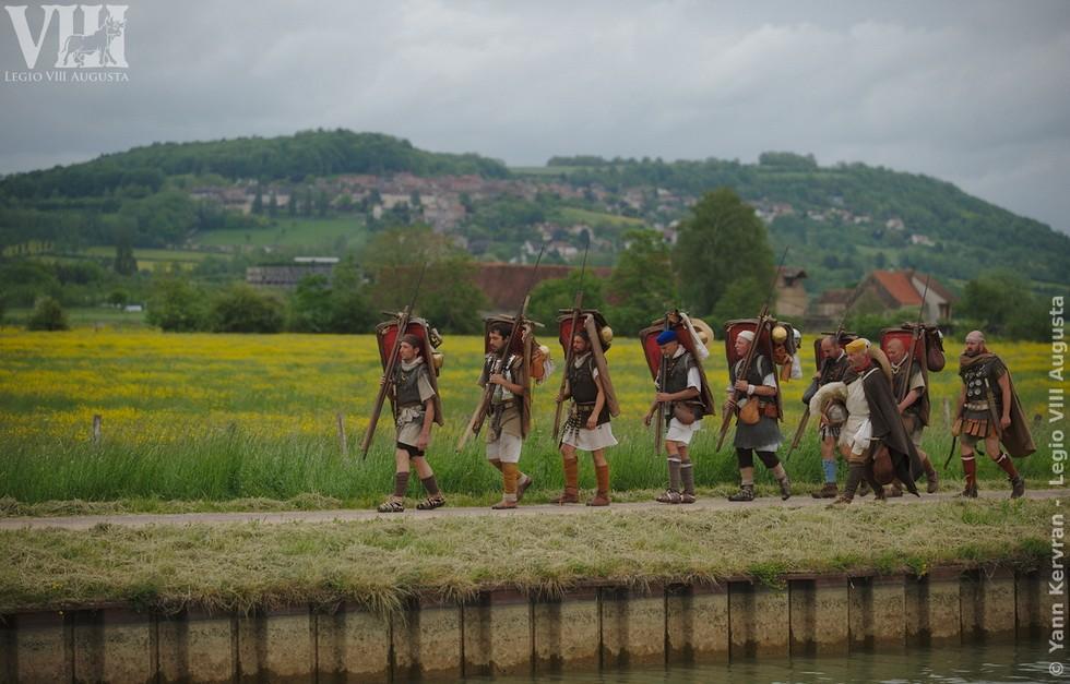 les légionnaires romains de la Legio VIII Augusta en marche dans la plaine des Laumes avec en fond l'Oppidum d'Alésia